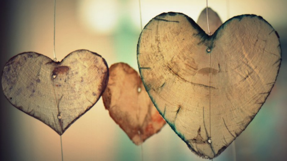Heart-shaped wooden cutouts hanging in front of a blurred background.