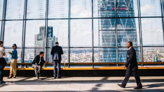 Businesspeople walk and stand in front of a large window in front of a city skyline.