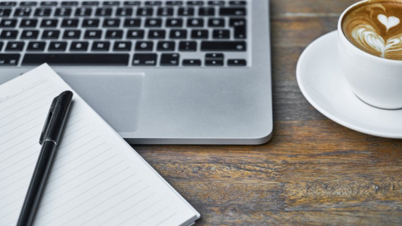 Cup of coffee, notebook, and laptop computer on a wooden desk.