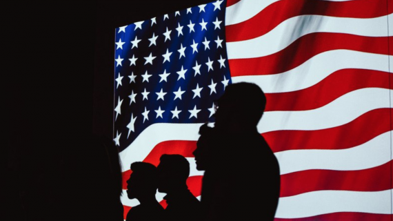 Silhouettes in front of an American flag screen.