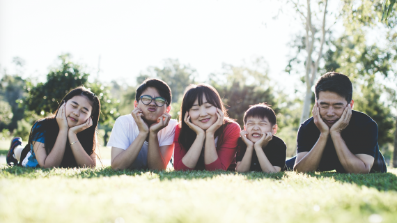 A smiling family laying on the grass next to each other.