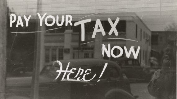 """Storefront window with """"pay your tax now here!"""" written on it."""