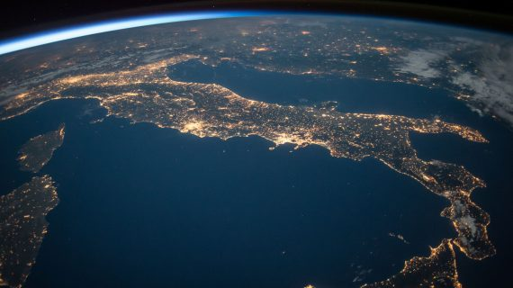 The Earth as it appears from space, with bright lights.