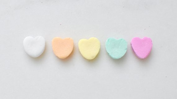 Candy hearts on a blank surface.