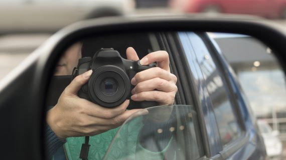 Reflection of woman holding camera in car mirror.