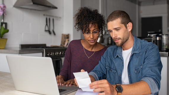 Young multiethnic couple checking bills while managing accounts on home banking app. Serious guy and african woman sitting at home discussing finance for the month. Young casual man and girl using laptop while looking at invoice and plan the budget to save.