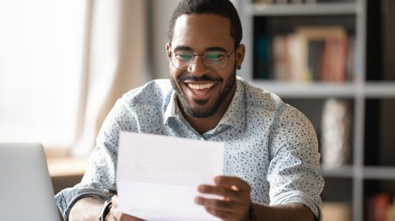 Cheerful happy young african american male student worker entrepreneur holding document bill read great news in letter receive loan approval scholarship salary payment concept sit at home office desk